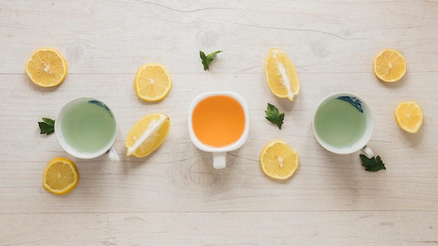 Different types of tea in ceramic cup with leaves and lemon slices on wooden table Free Photo