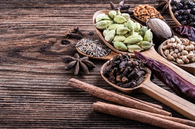 Different types of whole indian spices in wooden background close-up. Premium Photo