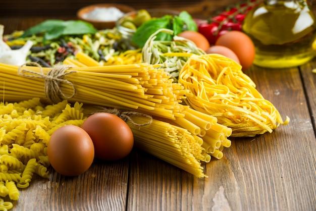 さまざまな種類のパスタとテーブルにバジルとオリーブ、鶏の卵 Premium写真