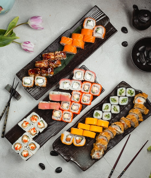 Different variety rolls with chopsticks on a black plate. Free Photo