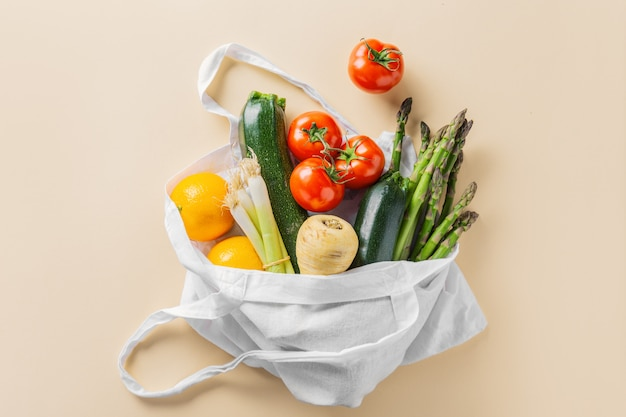 Different vegetables in textile bag on beige Premium Photo