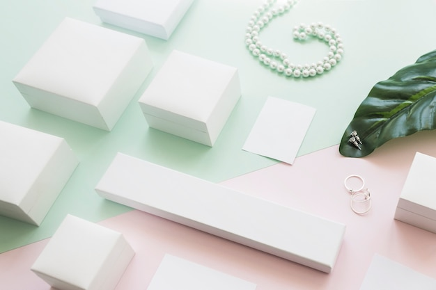 Different white boxes on leaf with jewelry on paper background Free Photo