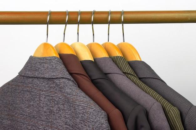 다른 여성용 사무실 클래식 재킷은 옷을 보관하기 위해 옷걸이에 매달려 있습니다. 세련된 옷 스타일 선택 프리미엄 사진
