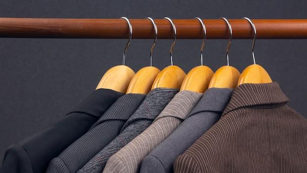 다른 여성용 사무실 클래식 재킷은 옷을 보관하기 위해 옷걸이에 매달려 있습니다. 세련된 옷 스타일 선택. 프리미엄 사진