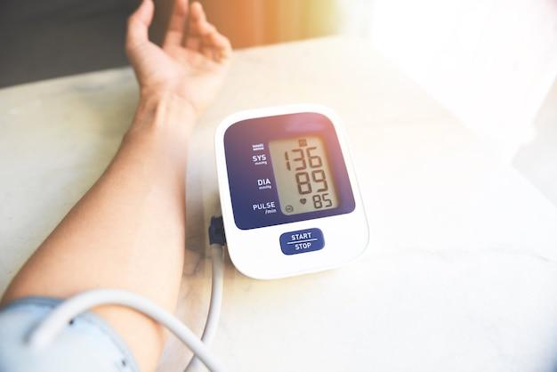 Цифровой монитор артериального давления на деревянном столе, медицинский электронный тонометр проверяет артериальное давление Premium Фотографии