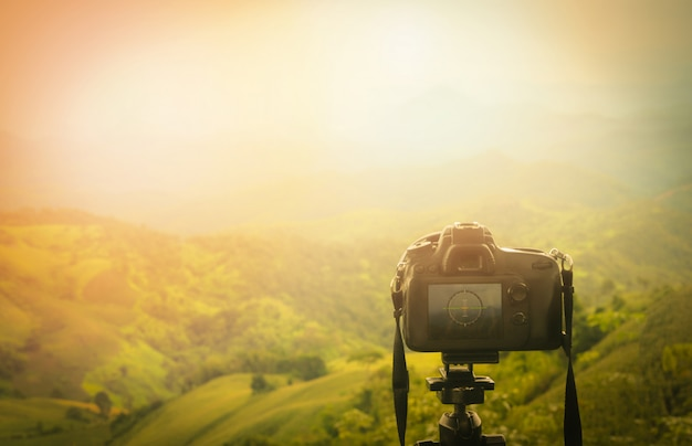 Digital camera professional / camera on tripod with view of mountain nature on background - take photos shooting nature Premium Photo