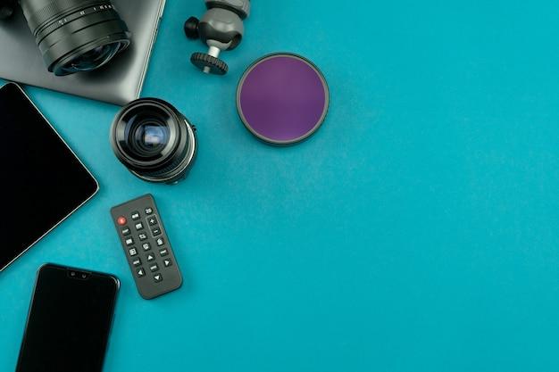 青い紙の背景にプロの写真家のレンズと機器を備えたデジタルカメラ Premium写真