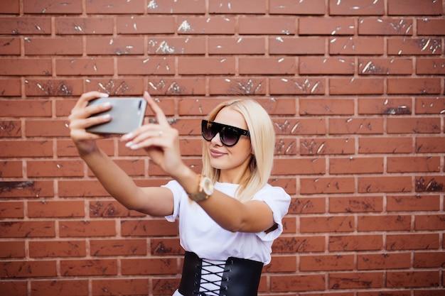 赤レンガの壁に対してselfieを取ってミレニアル女性のデジタル合成 無料写真