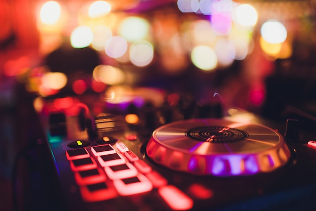 Digital midi controller panel with colorful disco light, dj turn table console sound equipment. Premium Photo
