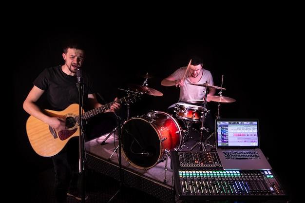 音楽を録音するコンピューターを備えたレコーディングスタジオのデジタルミキサー。背景には、ミュージシャンが楽器を演奏します。創造性とショービジネスのコンセプト。 無料写真