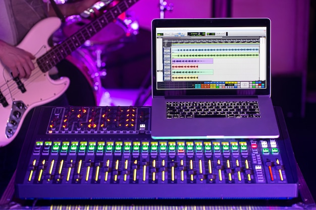 Digital mixer in a recording studio , with a computer for recording music. on the background of a man with a bass guitar. the concept of creativity and show business. Free Photo