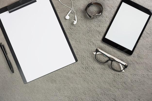 Digital tablet; clipboard; earphone; wrist watch; eyeglasses and pen on gray backdrop Free Photo