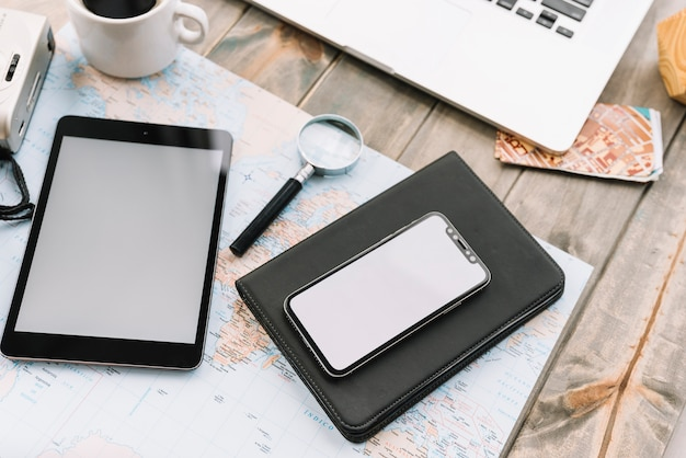 Digital tablet; magnifying glass and diary on map over the wooden table Free Photo