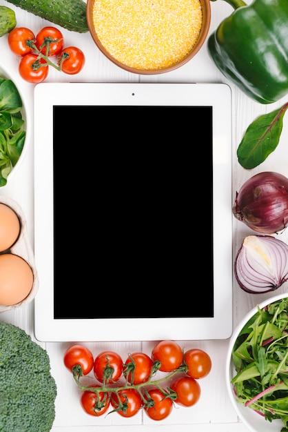 白い机の上の野菜に囲まれたデジタルタブレット 無料写真