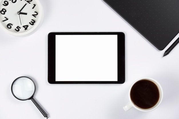 Digital tablet with alarm clock; magnifying glass; coffee cup and graphic digital tablet with stylus on white background Free Photo