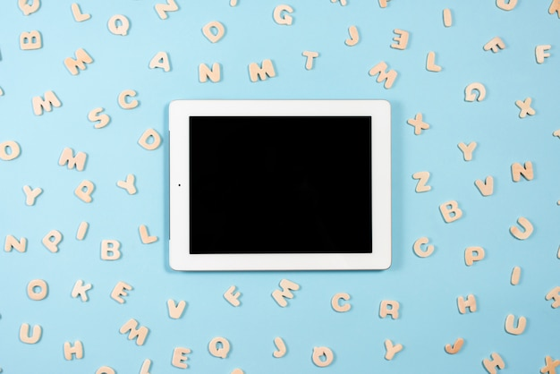 Digital tablet with black screen display surrounded with wooden letters on blue background Free Photo