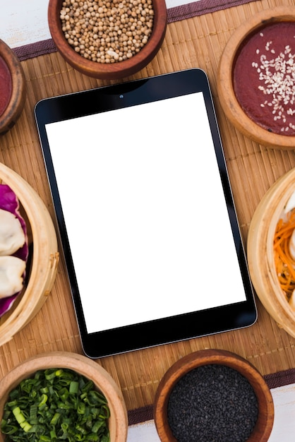 Digital tablet with white blank screen surrounded with steamers; coriander seeds; sesame seeds and spring onions on placemat Free Photo