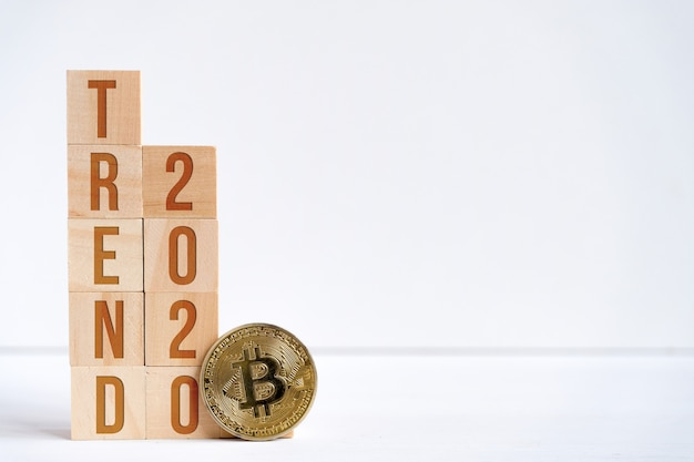 Digits 2020 and the word trend on wooden cubes on a white background next to a bitcoin coin. Premium Photo
