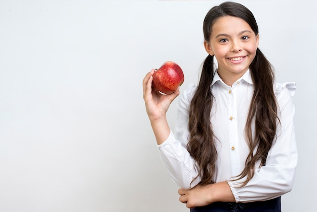 Diligent hispanic schoolgirl eating apple Free Photo