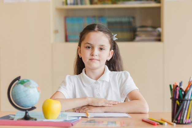 Diligent pupil sitting at desk Free Photo