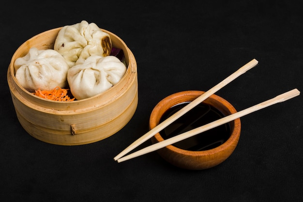 Dim sum along with carrot salad served in small steamer basket and soya sauce bowl with chopsticks on black background Free Photo