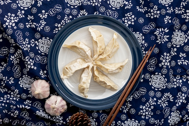 Dim sum in a white plate with garlic on a floral blue background Free Photo