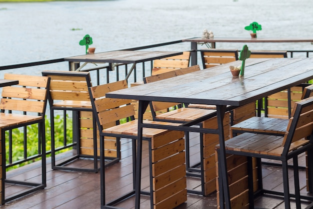 Dining table in the cozy outdoor cafe. dining table beside the river cafe. Premium Photo