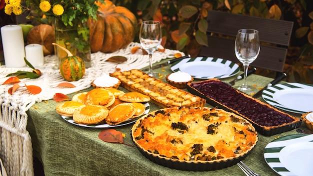 Обеденный стол для семейного отдыха на заднем дворе осенью. Premium Фотографии