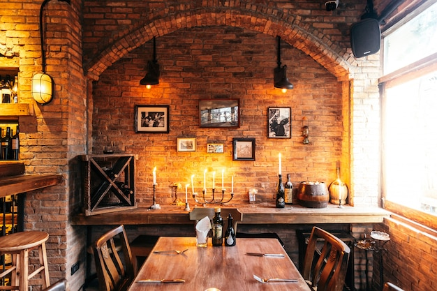 Dining table of italian restaurant decorated with brick and photo frames in warm light. Premium Photo