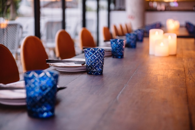 Dining table set including white plate, cutlery and blue glass on the wooden table. Premium Photo