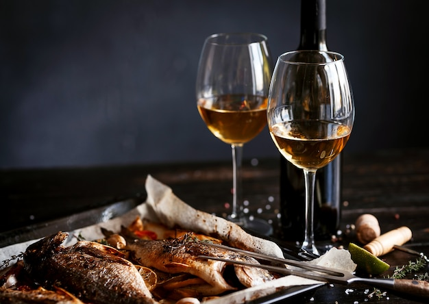 Dinner concept with two glasses of white wine, baked fish Premium Photo