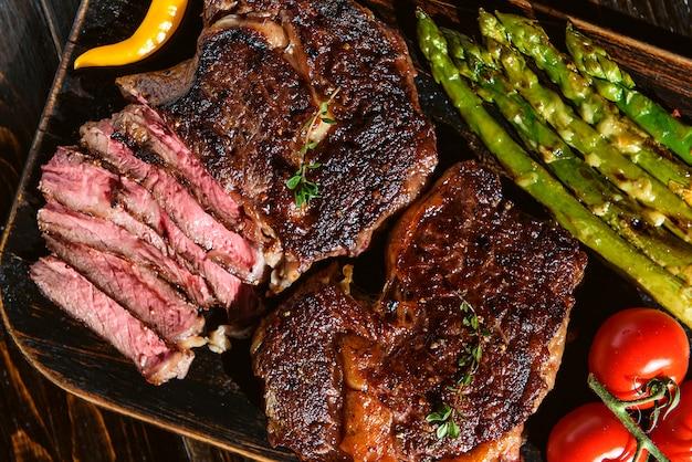 두 가지 맛있고 맛있는 스테이크, 치즈와 야채를 곁들인 아스파라거스를위한 저녁 식사. 프리미엄 사진