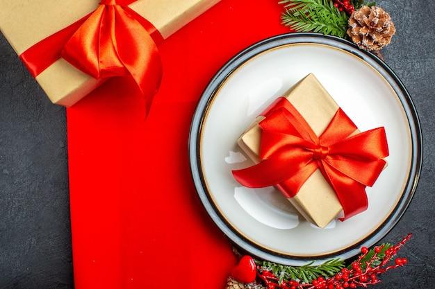 빨간 냅킨에 장식 액세서리 침엽수 콘과 그것에 선물 및 전나무 가지에 선물 디너 플레이트 무료 사진