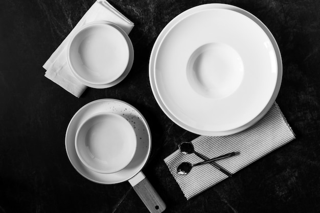 Dinner set on a dark , empty white plate with  fork and spoon Premium Photo