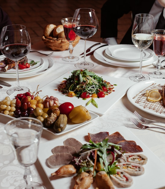 Dinner setup with red wine, pickle plate, meat plate, fresh salad Free Photo