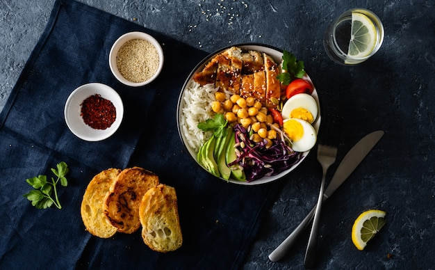 Dinner table buddha bowl rice chickpeas chicken breast eggs vegetables top view Premium Photo