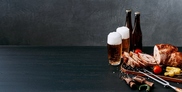 Dinner for two of meat and craft beer. two glasses of beer, baked chopped meat with vegetables on a wooden tray with a meat fork and spices Premium Photo
