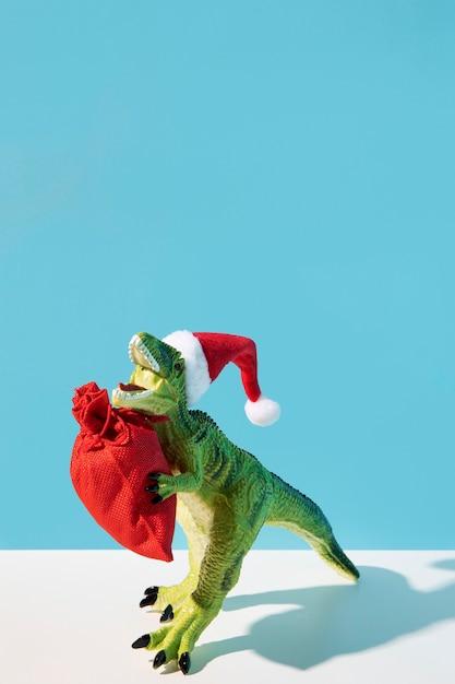 赤い袋を保持している恐竜のおもちゃ 無料写真