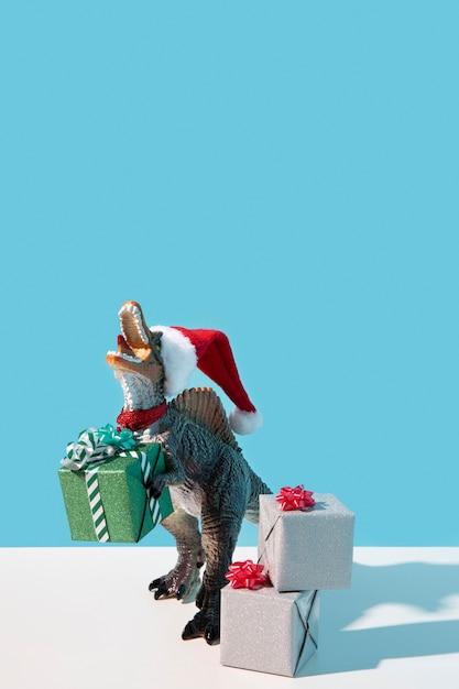 Giocattolo del dinosauro che porta il cappello della santa Foto Gratuite