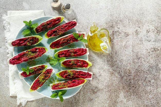 Dip of boiled beets and pistachios in leaves of belgian endive with mint. healthy summer snack Premium Photo