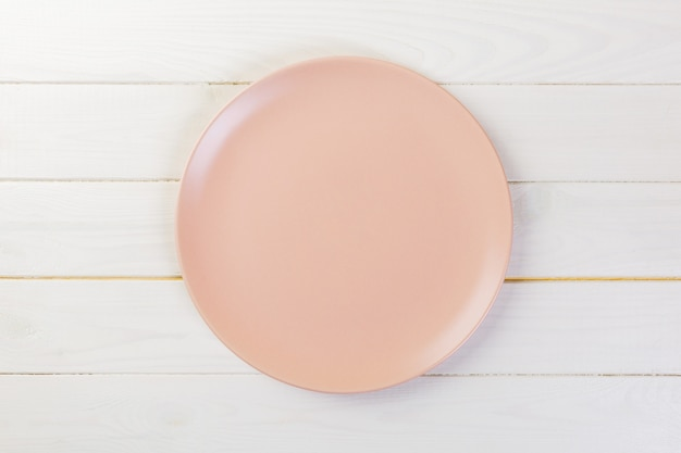 Directy above empty rose matte dish for dinner on white wooden Premium Photo