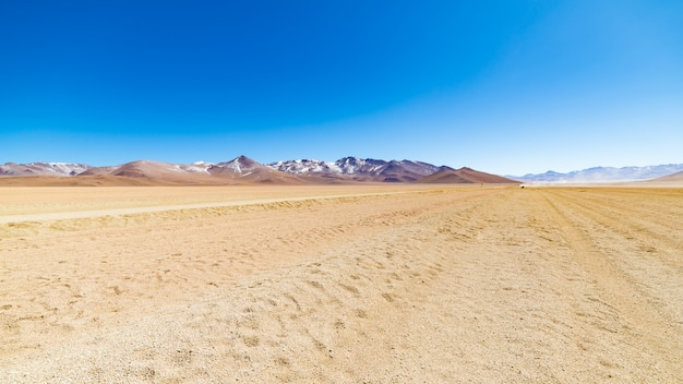 Dirt road at high altitude with sandy desert and barren volcano range on the andean highlands Premium Photo