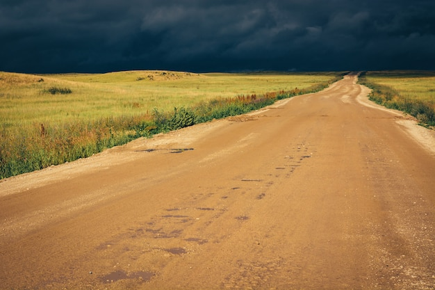 Dirt road to the horizon line under dramatic dark storm clouds. Premium Photo