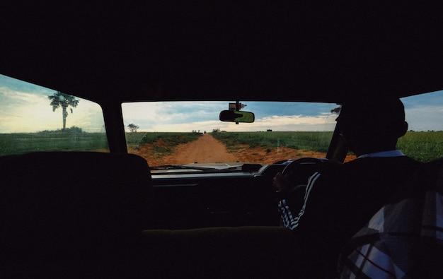 男性運転の車から撮影した草原の真ん中にある未舗装の道路 無料写真