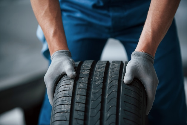 Dirt on the wheel. mechanic holding a tire at the repair garage. replacement of winter and summer tires Free Photo