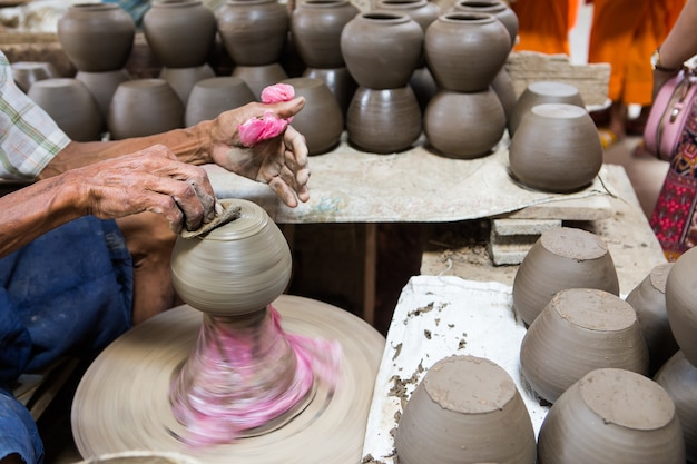 Dirty hands making pottery in clay on wheel Premium Photo