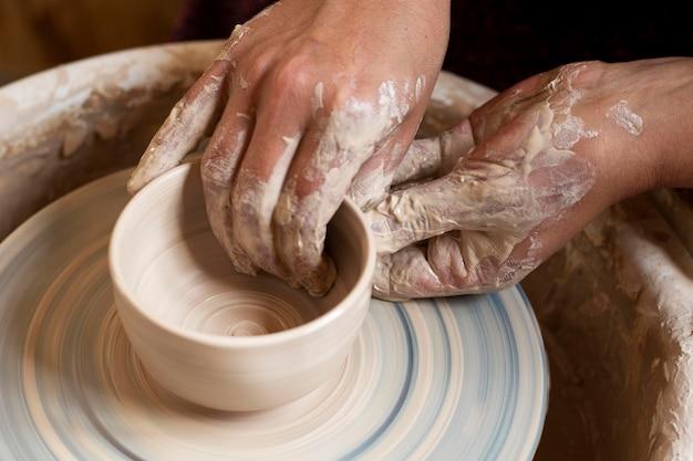 Mani sporche che modellano in argilla su un tornio da vasaio Foto Gratuite