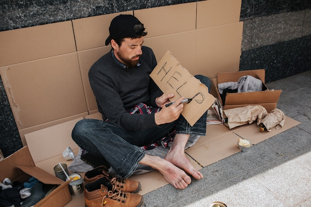 Dirty homeless man is sitting on cardboard and writing down the word help on a piece of paper Premium Photo