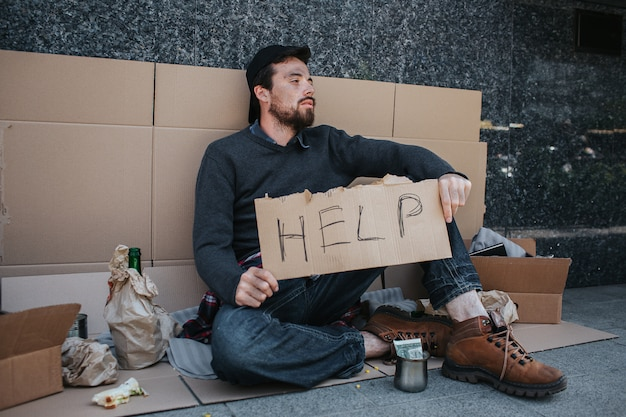 Dirty man is sitting on the ground and holding a help cardboard in hands. he is looking to the side. there are lots of stuff near him. also there are a cup with money in front of him. Premium Photo