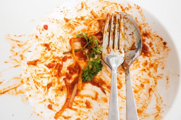 Грязная белая тарелка. после еды спагетти красного соуса. вид сверху. ложка  и вилка с пищевыми отходами.   Премиум Фото